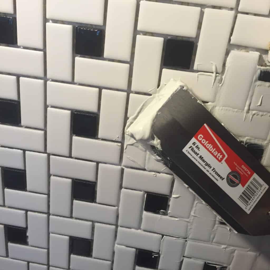 applying grout to tile backsplash