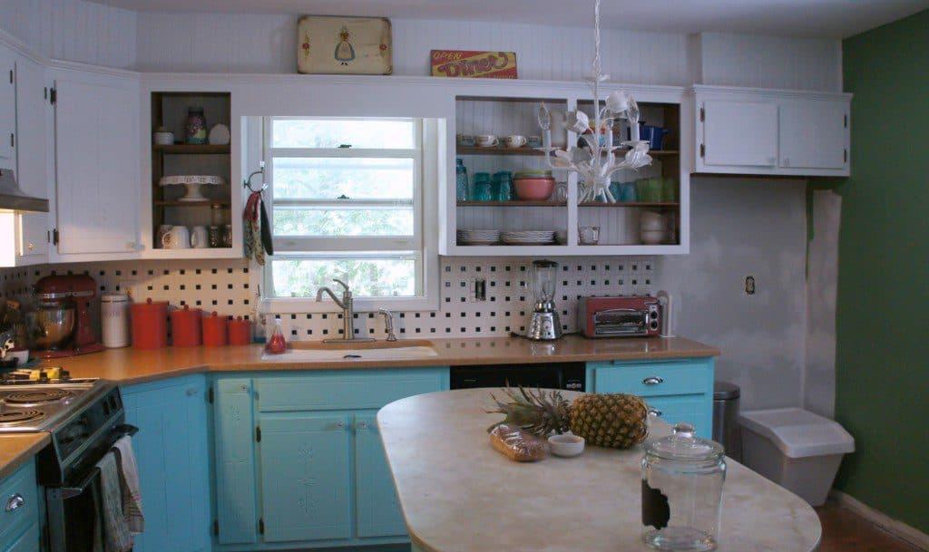aqua kitchen cabinets and black and white tile backsplash