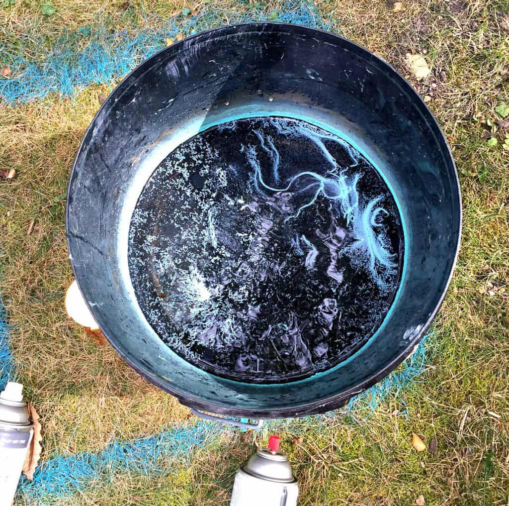 spray paint into bucket of water