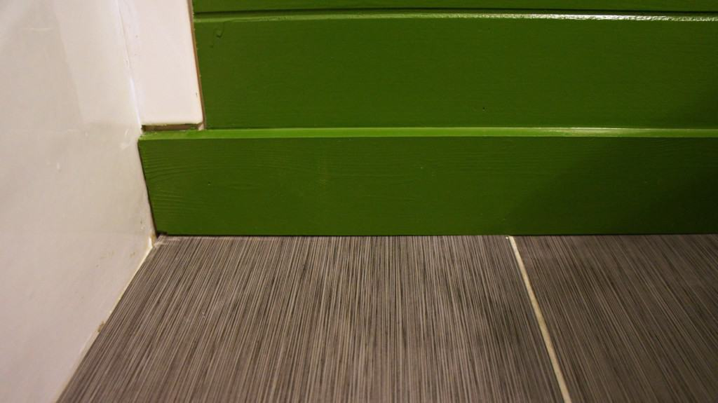 gray tile floor with green shiplap