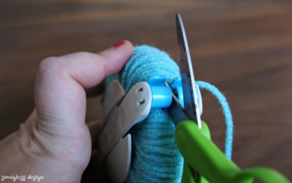Cut the yarn on the pom pom maker