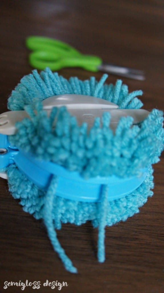 Tie yarn around pom pom maker