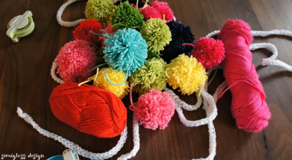 Learn how to make a pom pom! Create fun decor with this easy DIY project that can be done while watching television! Making pom poms is fun and addictive!