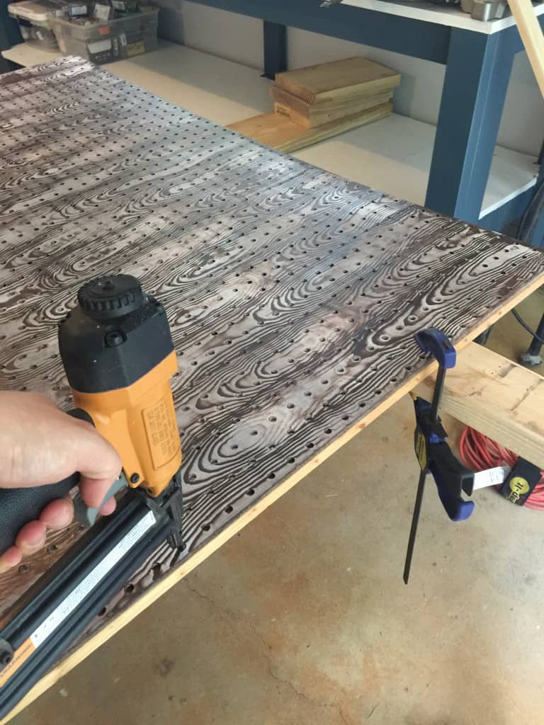 Using a nail gun to attach pegboard panel to the wood frame