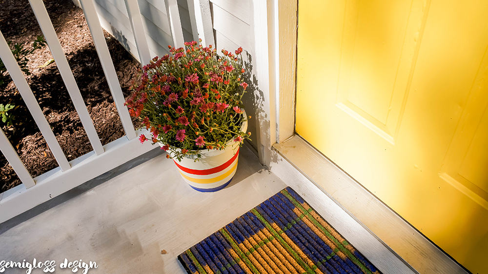 yellow front door with plaid door mat