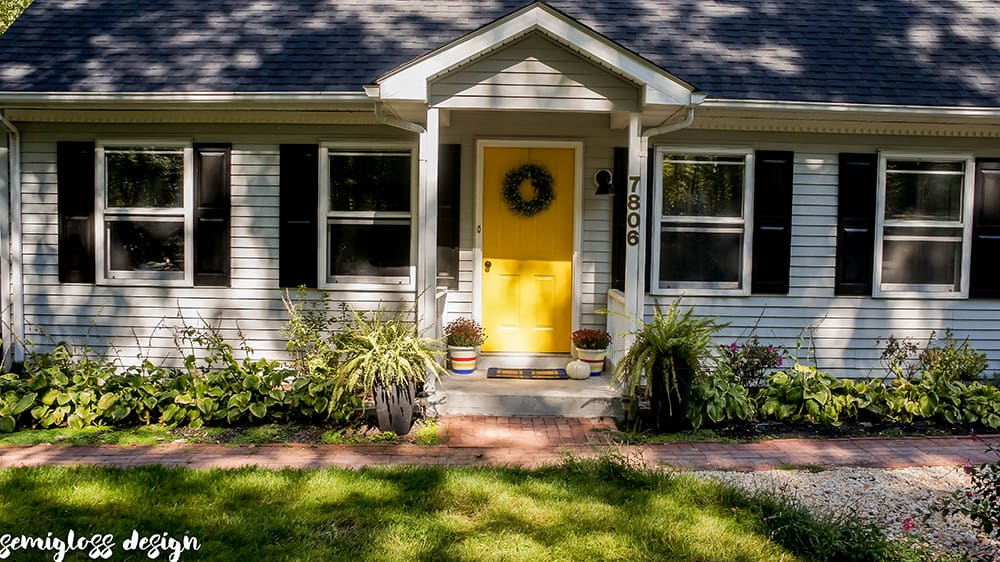 Updated curb appeal picture with yellow front door and black shutters