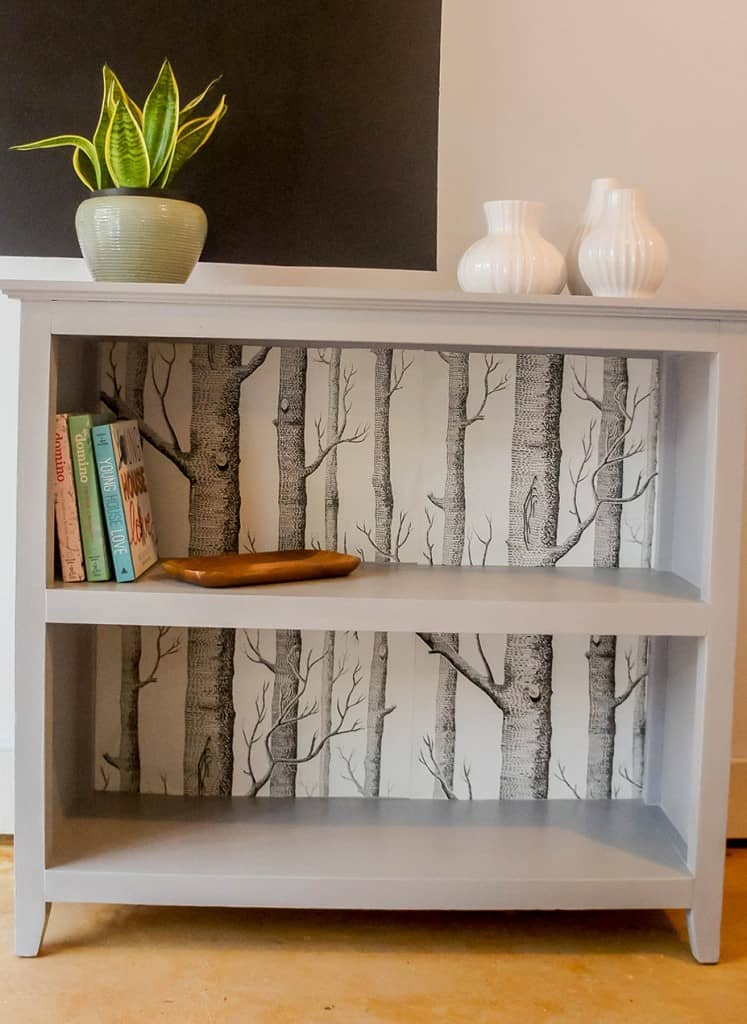 Painted bookcase with tree wallpaper backing