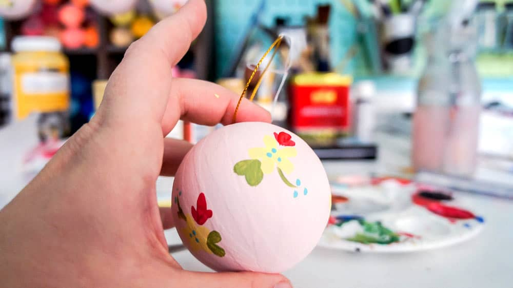 Make your own hand painted floral ornaments. This easy technique works for non-artists too. #decoartprojects #christmasornaments #diychristmasdecor #handpaintedflorals