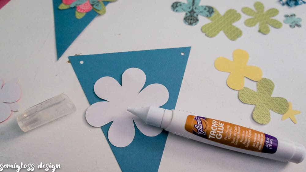 Make your own paper flower banner for spring. This fun DIY spring decor project is simple and budget friendly. Free flower cut files. #cutfile #papercrafting #banner #springdecor