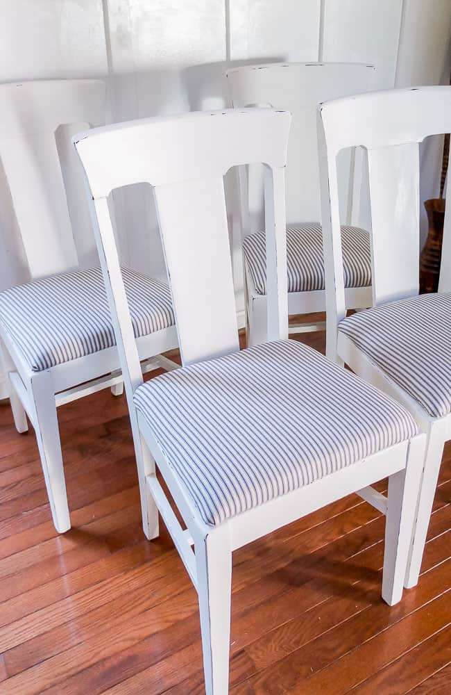 White distressed chairs with ticking upholstery