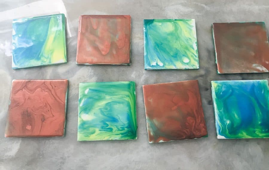 finished paint pour coasters in shades of blues and copper