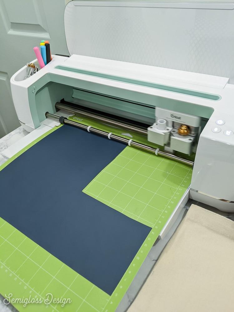 iron-on vinyl on mat being cut by cricut maker