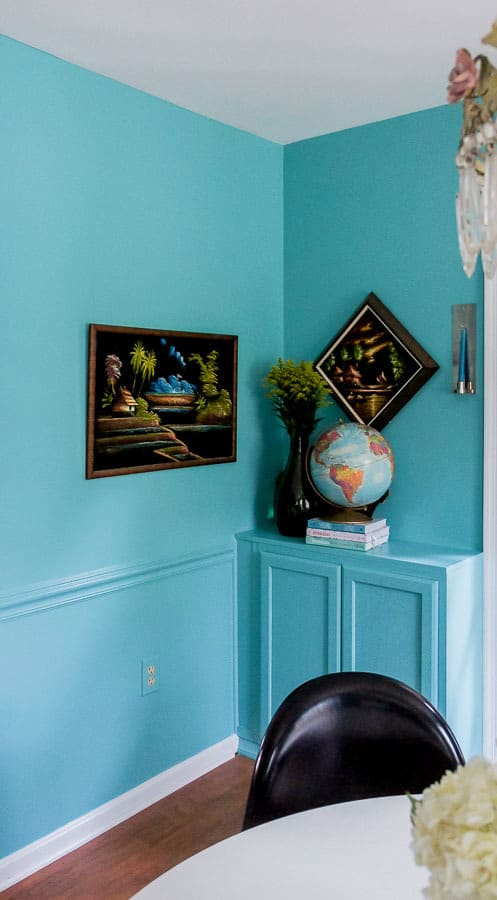 vintage art on teal walls with built in cabinets