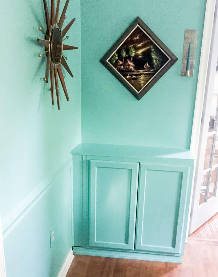teal cabinet on wall with painting