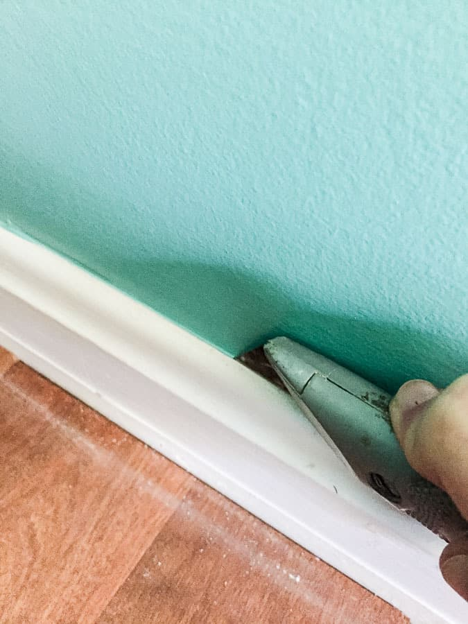 Cut along molding to remove without damaging walls
