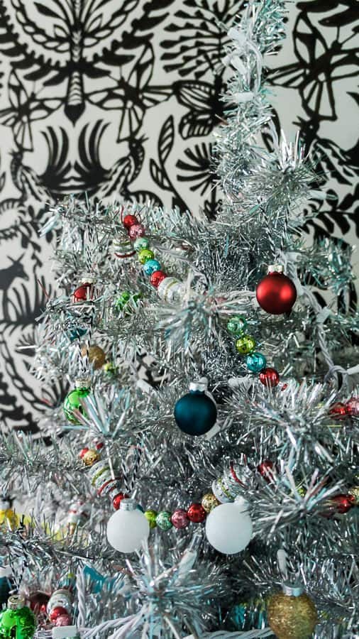 shiny bright ornaments on tinsel tree