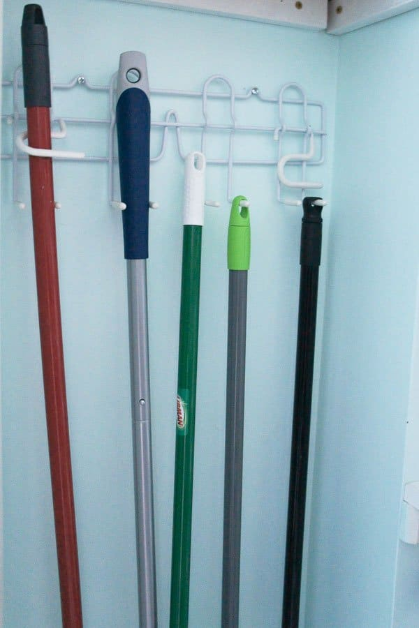 a broom holder holds brooms and mops