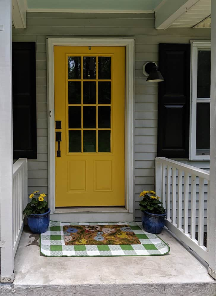 front porch makeover after with layered rugs and potted flowers