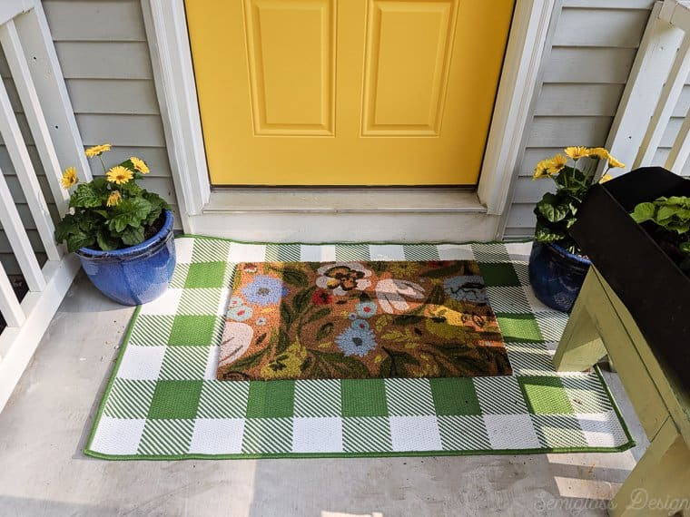 Layered rugs using a buffalo check rug with a floral doormat in front of a yellow front door.