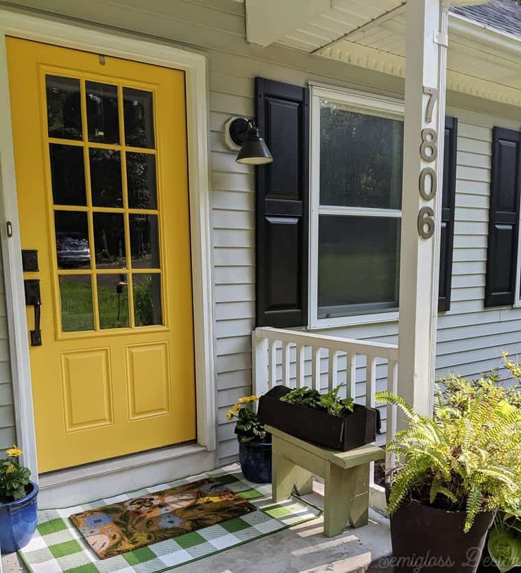 front porch makeover featuring yellow front porch, layered rugs, toolbox planter and potted daisies.