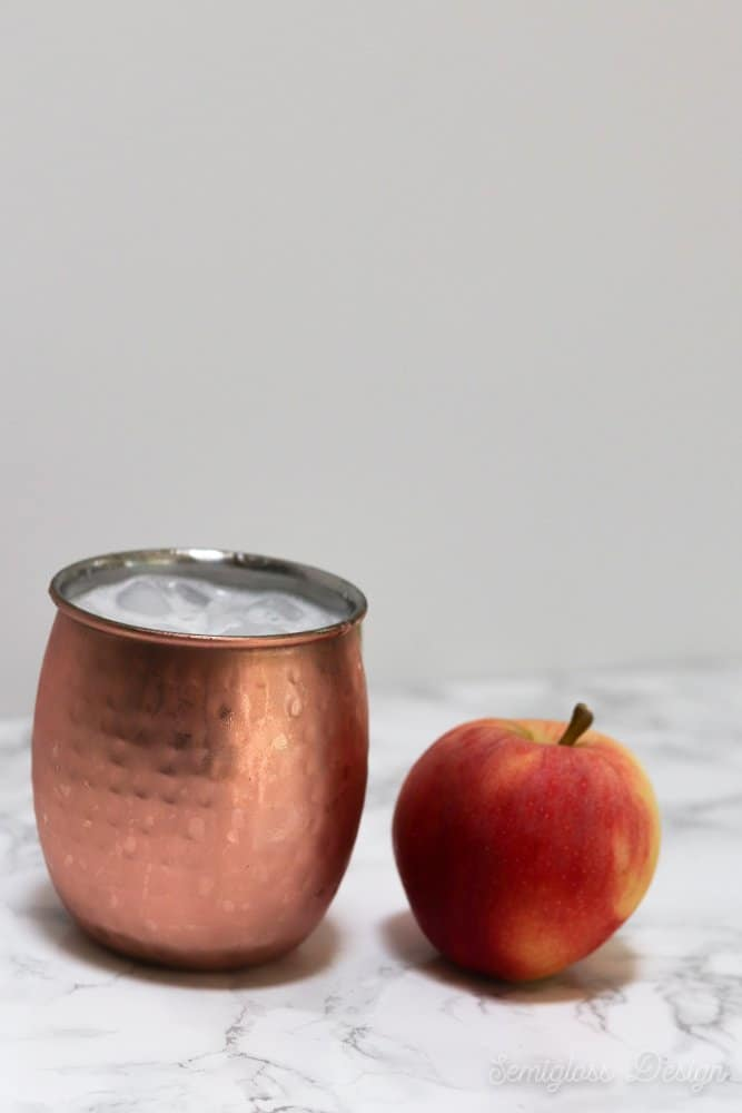apple cocktail in copper mug with apple