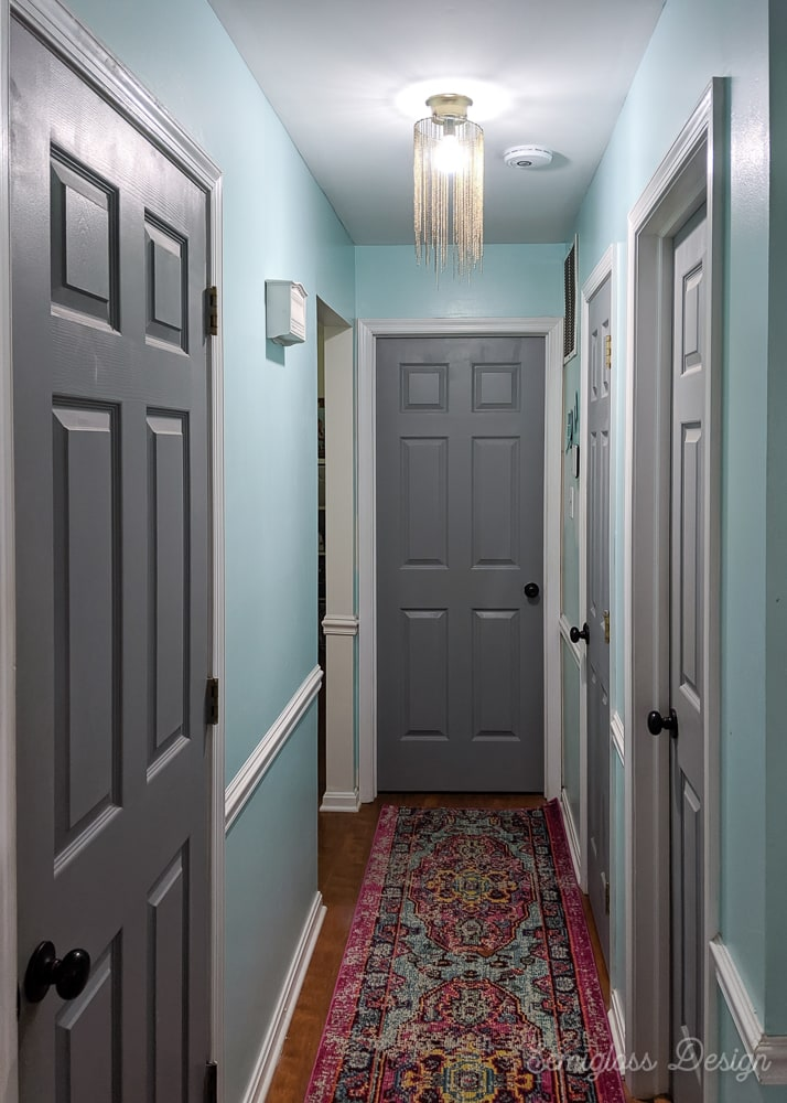 hallway painted aqua with pink rug and gray doors