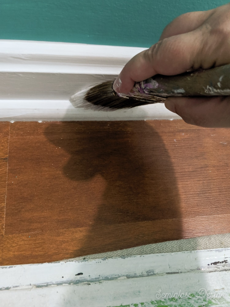 painting baseboard trim with paint brush