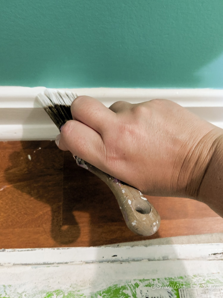 painting baseboards white with a paintbrush