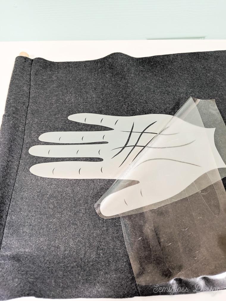 peeling away plastic from htv design of hand