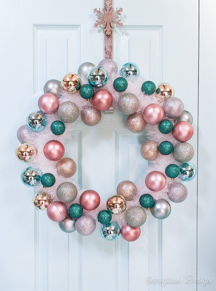 ornament and tinsel wreath on light blue door