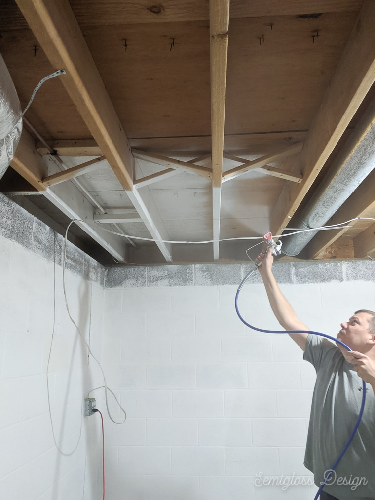 man spraying paint on exposed ceiling in basement