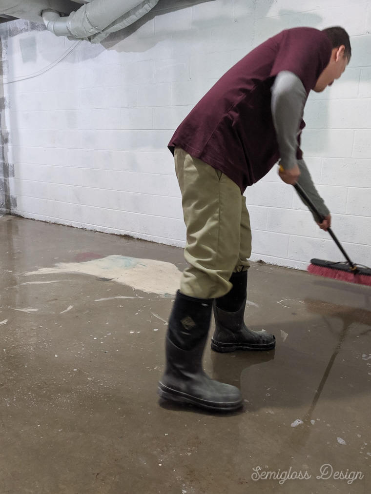 using push broom to scrub concrete floor