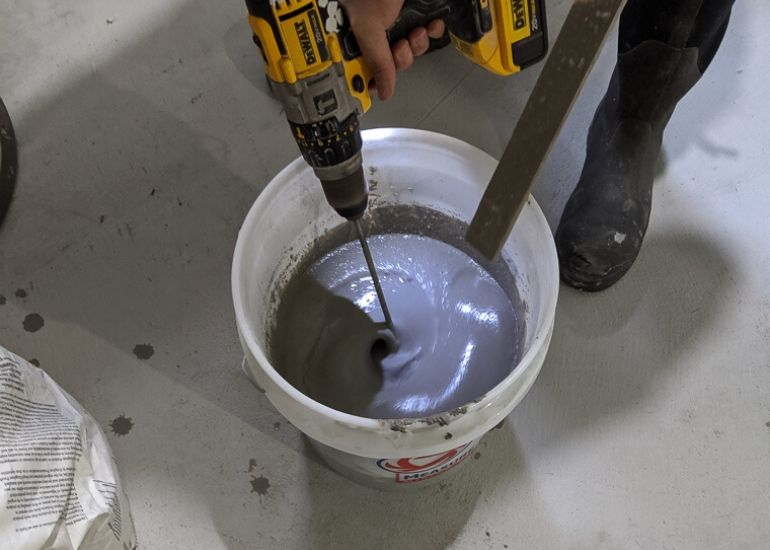 mixing concrete to refinish basement floor