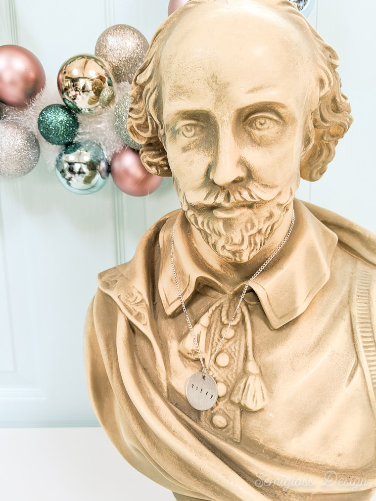 stamped metal necklace on Shakespeare bust
