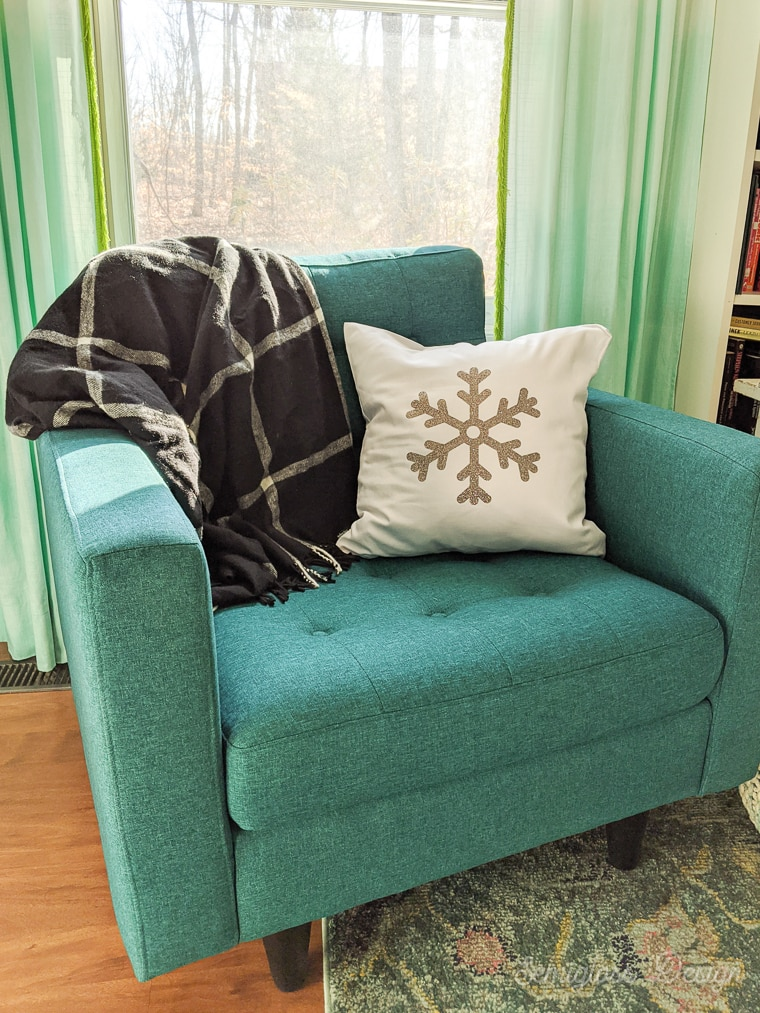 snowflake pillow and plaid throw on teal chair