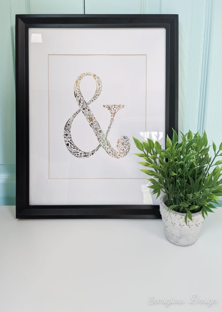 gold foil ampersand art in frame with plant