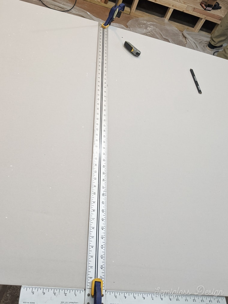 using a t-ruler to cut drywall