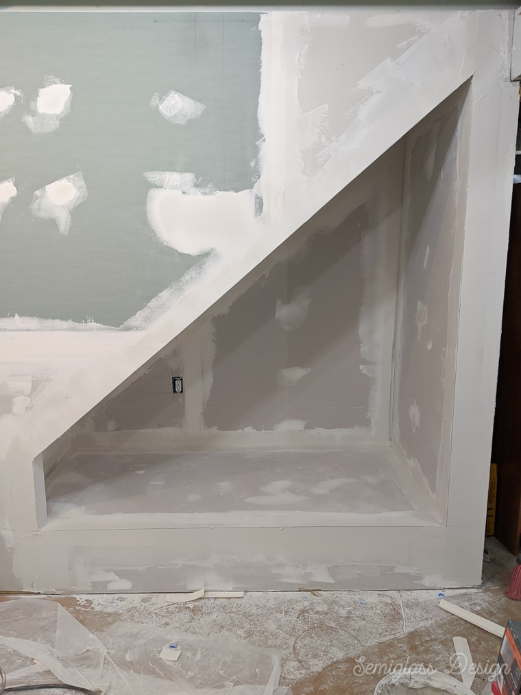 nook under stairs with drywall mudded and taped