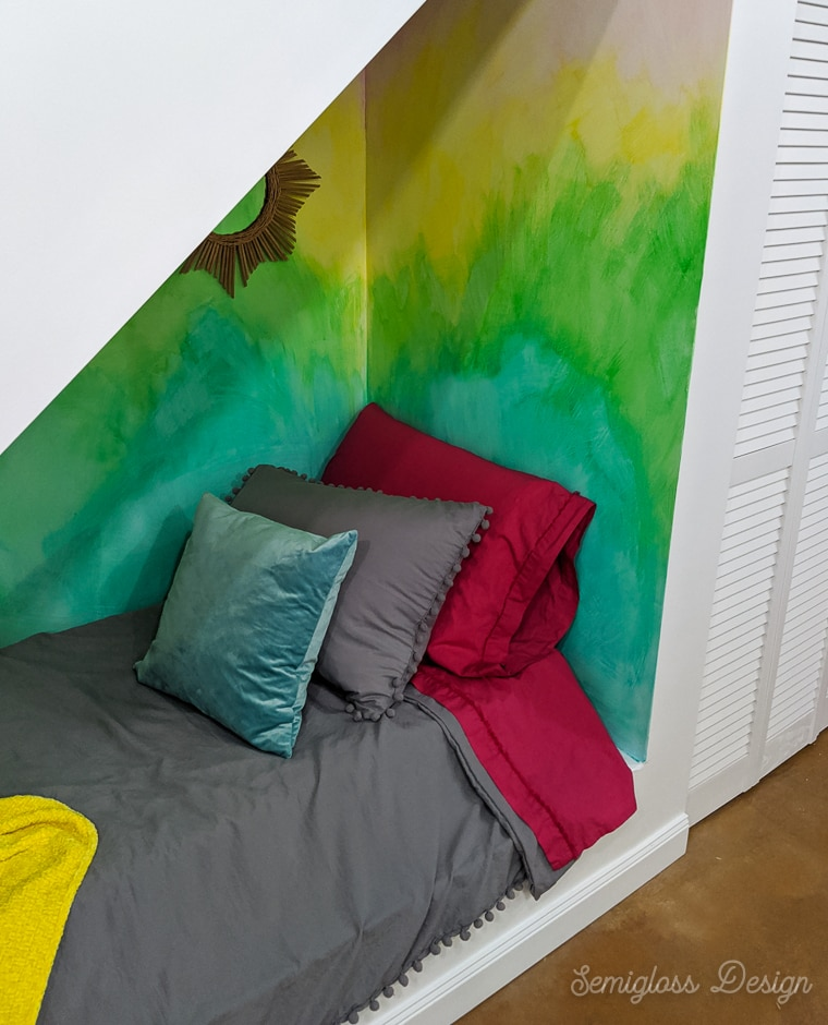 colorful nook with bed under stairs