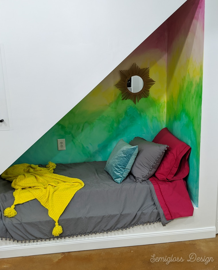 sleeping area under stairs with rainbow mural