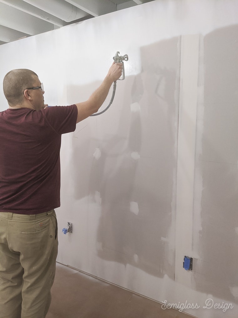 man spraying paint on drywall