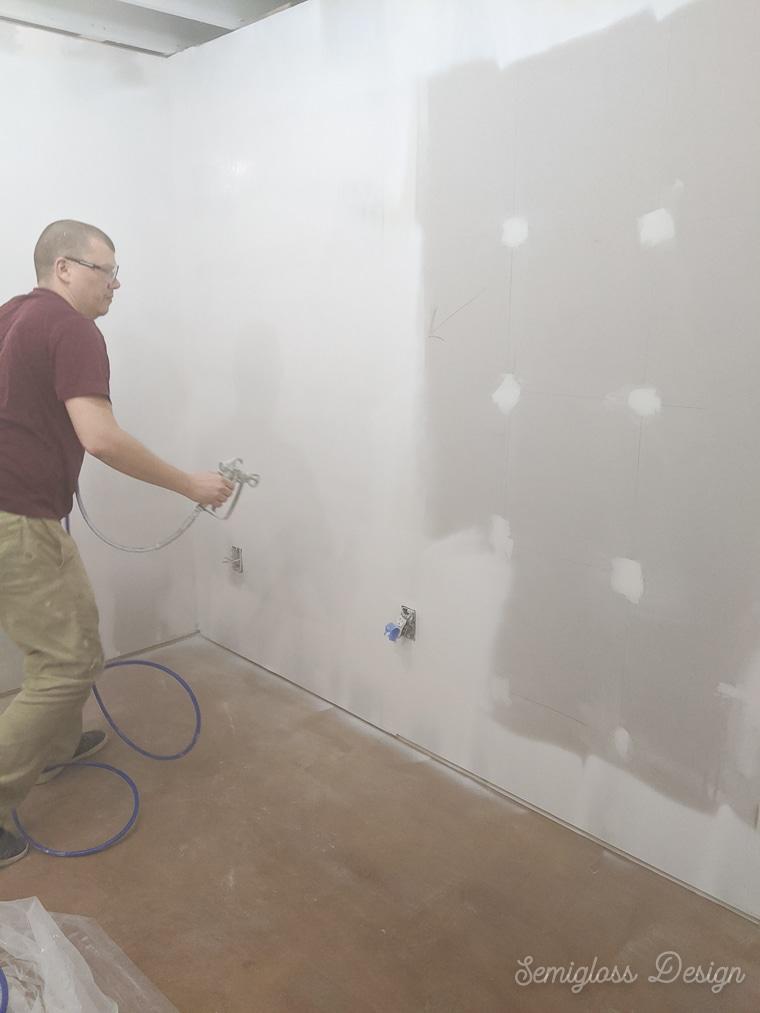 man spraying walls white