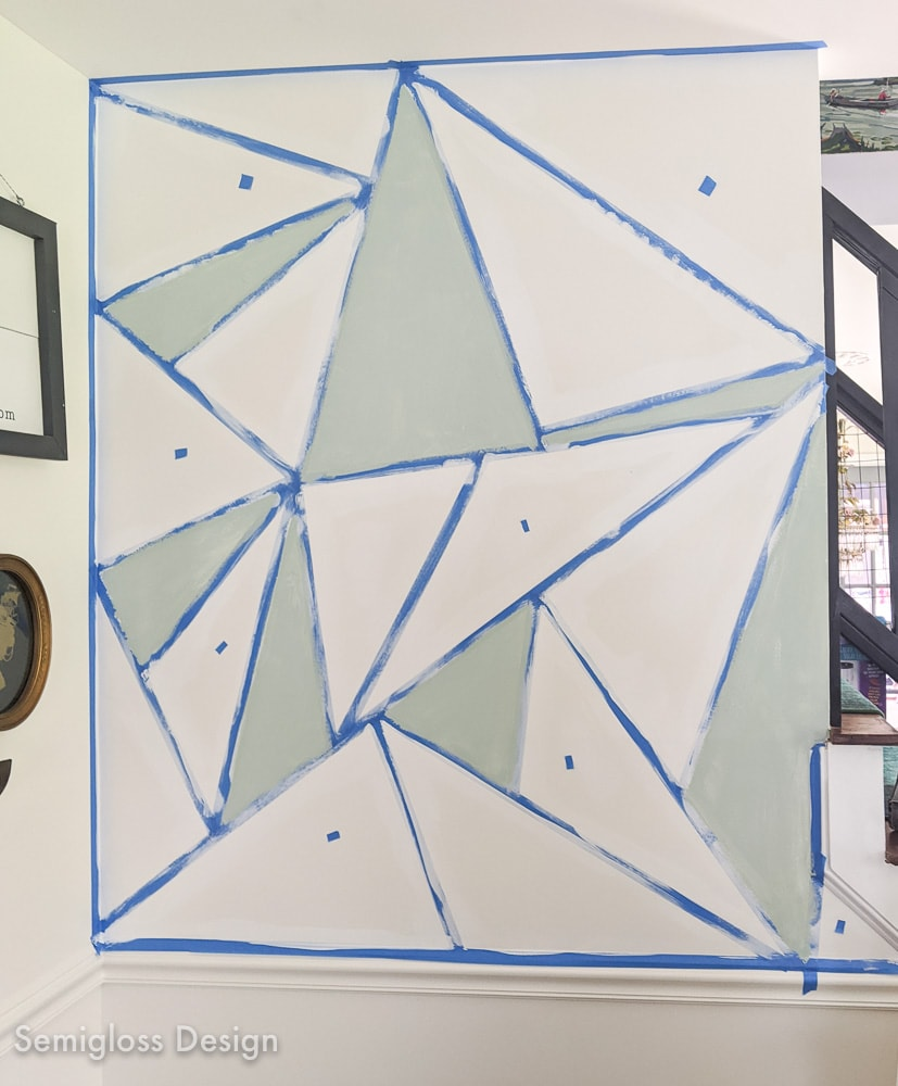 painting a pale teal color onto geometric mural