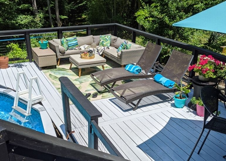 gray deck with modern furniture by pool