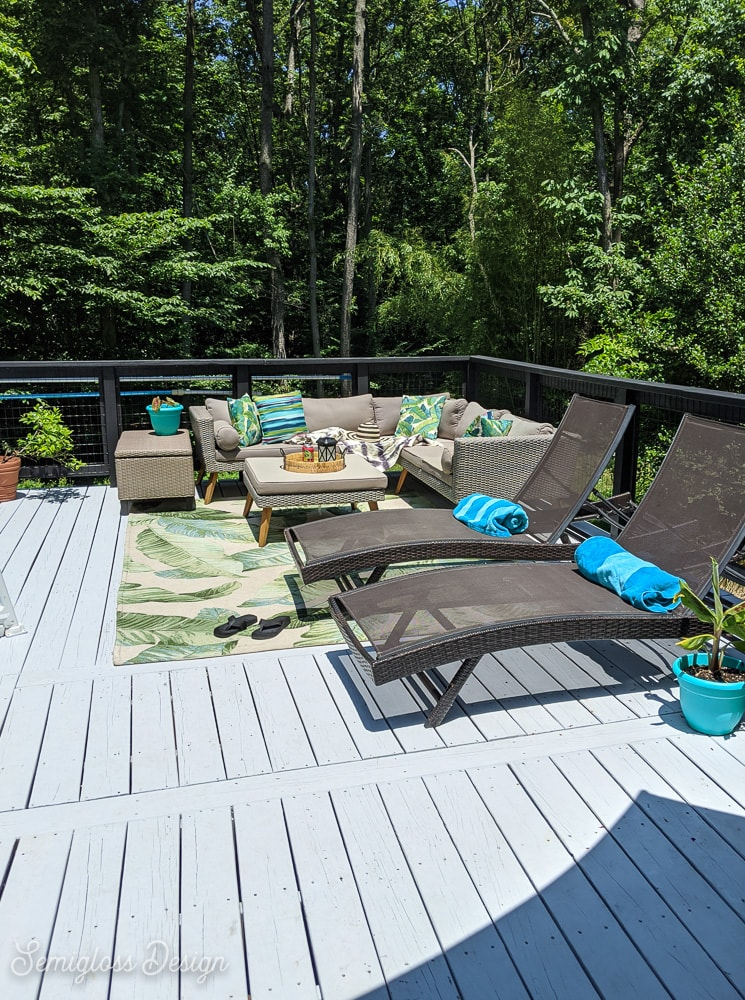 deck painted gray with modern black railing and furniture