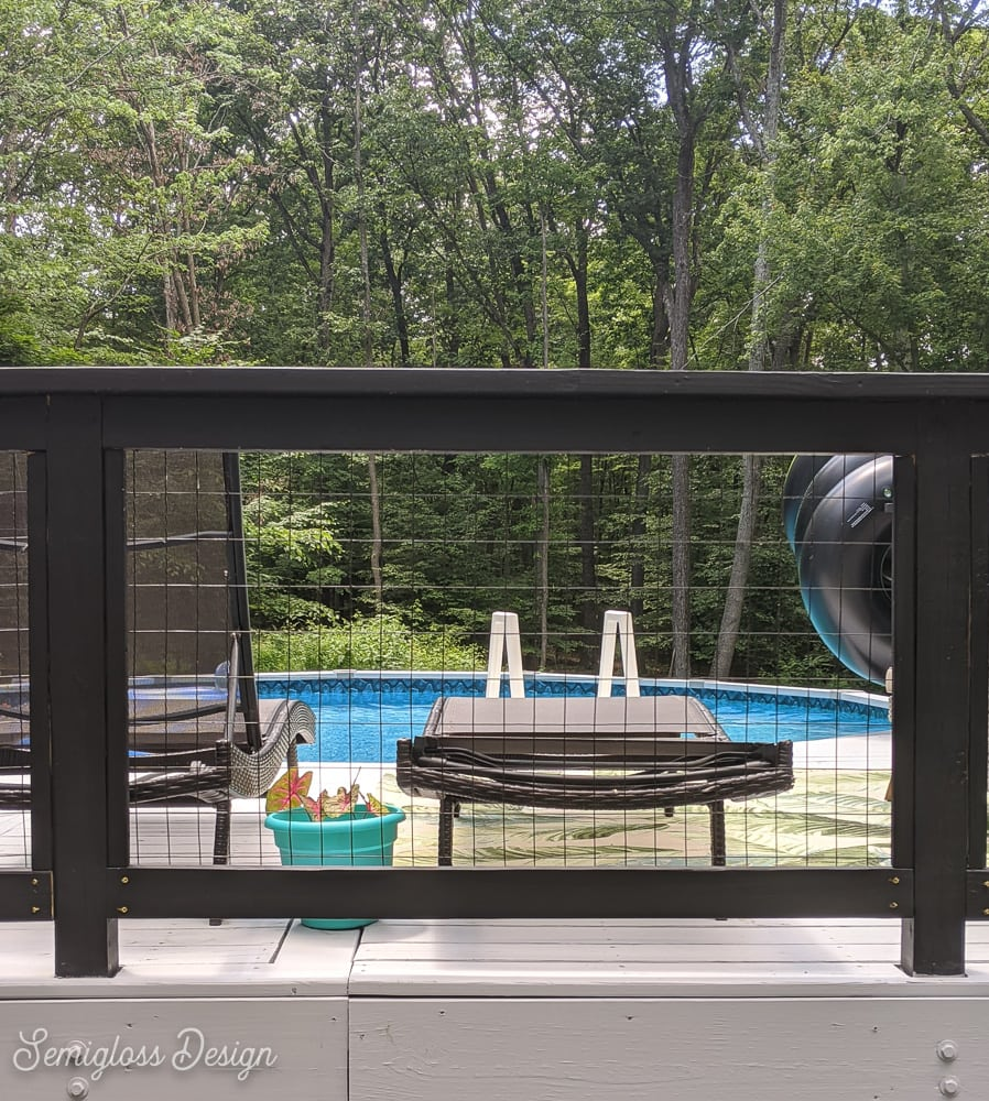 black modern railing on deck with pool in background