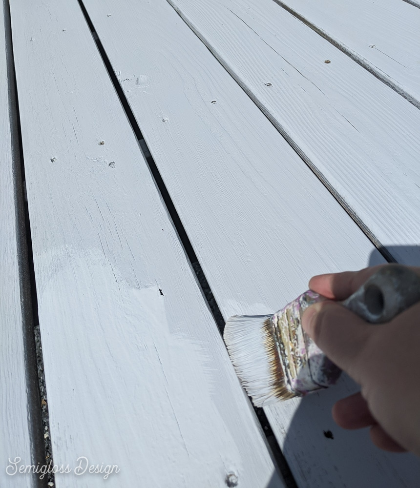 painting cracks of deck with paint brush