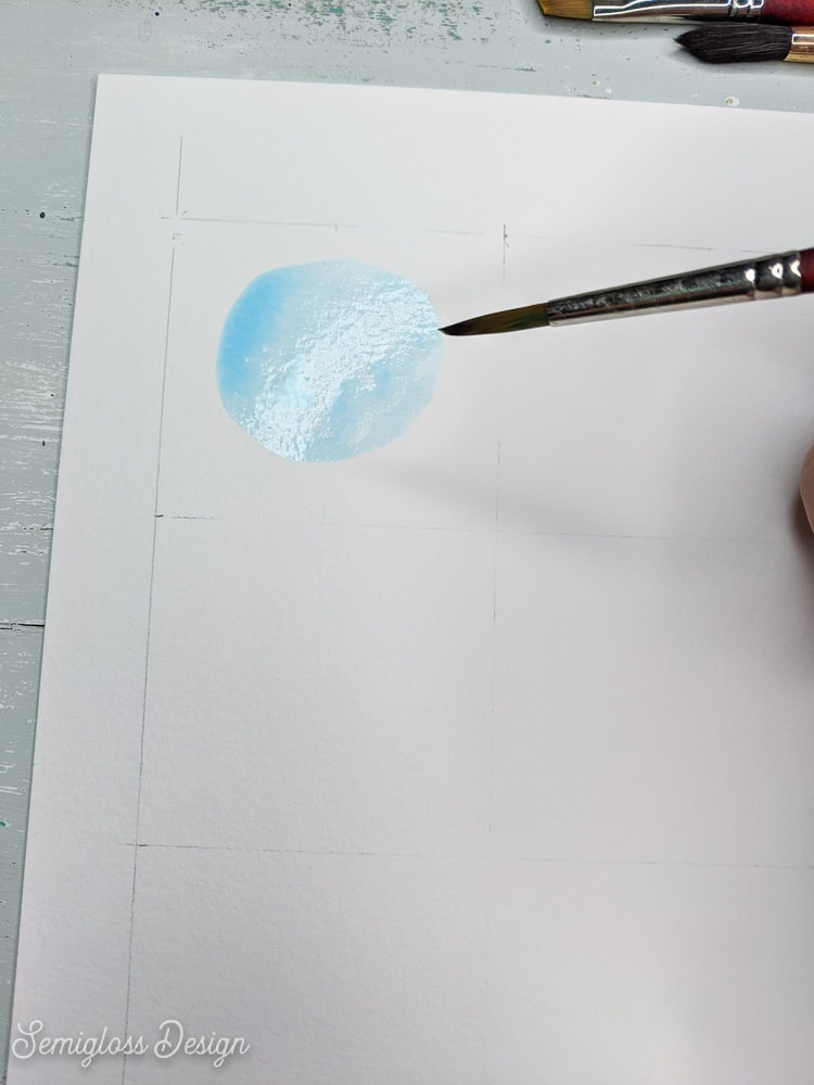 painting a blue circle with watercolor paint