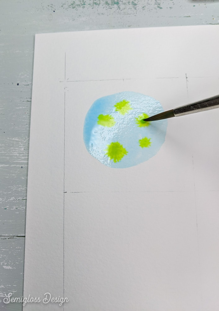 painting dots of green in blue watercolor circle