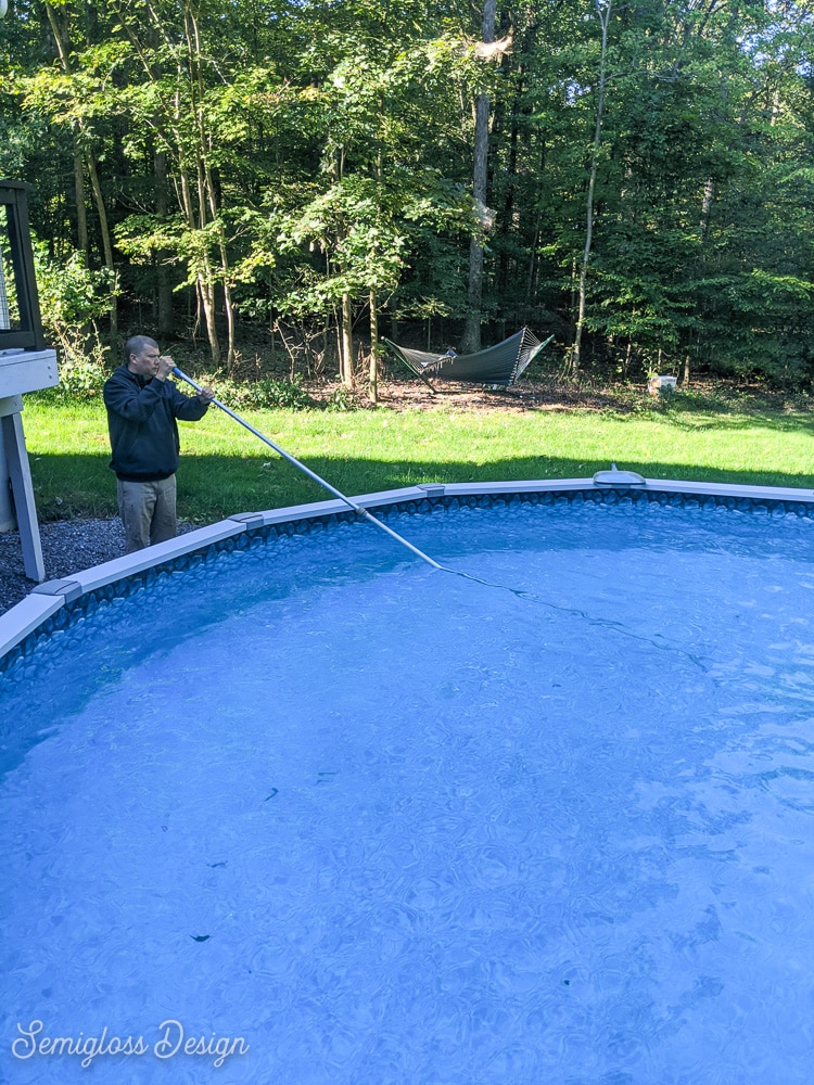 man cleaning pool with brush